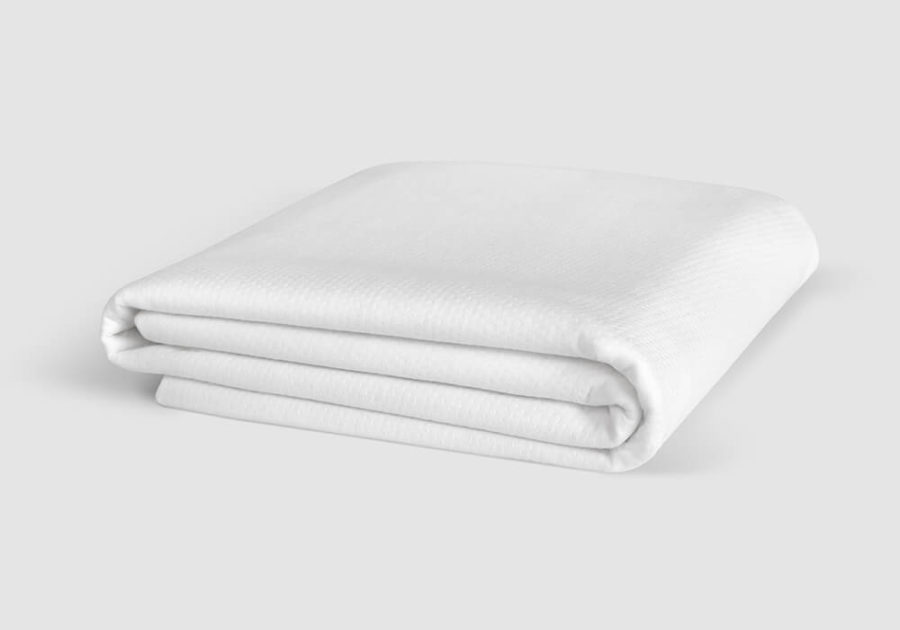 Folded mattress protector against a white background.